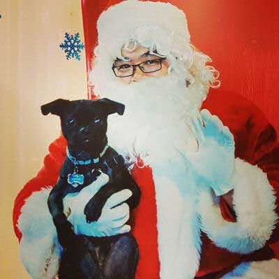 santa with a small black canine